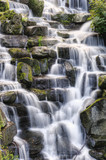 Beautiful waterfall cascades over rocks in lush forest landscape