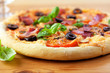 Pizza with tomatoes and ham on wooden background