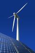 Solarmodule und Windkraftrad vor blauem Hintergrund