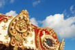 Fancy gold Carousel trim and a blue sky with white clouds