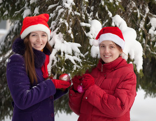 women  in  christmas hats decorates  spruc