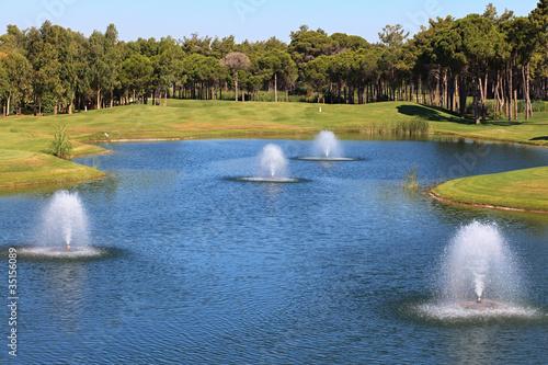 Leinwanddruck Bild Fountain in the artificial pond.