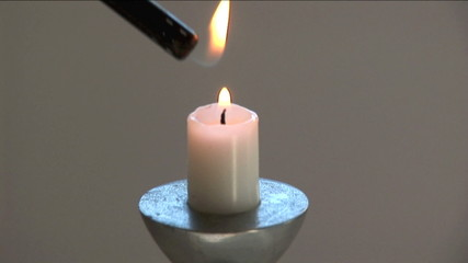 Electronic lighter being put to and lighting a candle.
