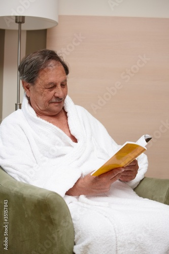 Old man in armchair reading a book