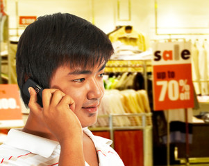 Young Man On The Phone In Front Of A Store