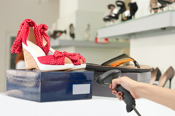 Cropped view of shop assistant scanning code on shoe box