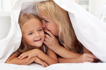 Woman and little girl sharing a secret