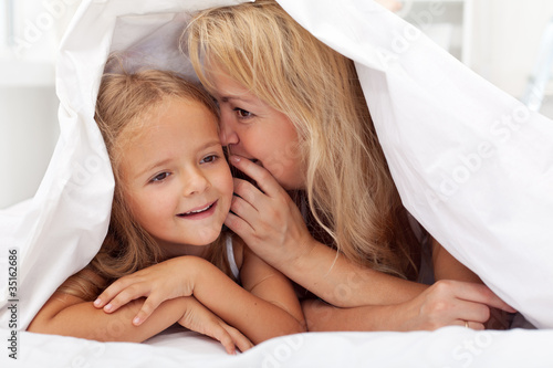 Woman and little girl sharing a secret