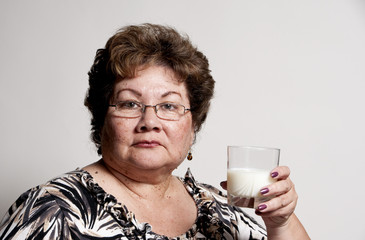 a Hispanic woman ready to drink a glass of milk.