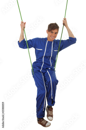 young man in blue coveralls in acrobatic tricks on rope, series