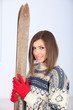 smiling young woman in sweater holding old wooden ski.