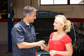 Young woman collecting car from repair shop