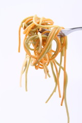 Cooked colorful Spaghetti hanging on a fork