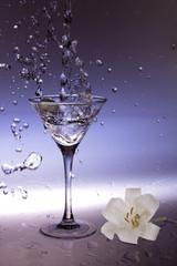 Splashing olive into a martini glass