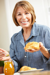 Mid age woman eating croissants