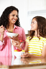 Mother and daughter eating cereal and fruit