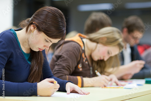 pretty female college student sitting in a classroom