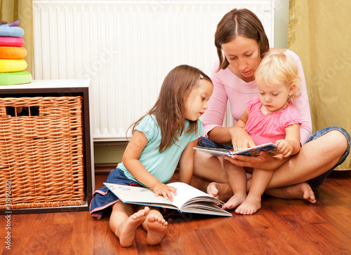 mother with her daughters reading a book