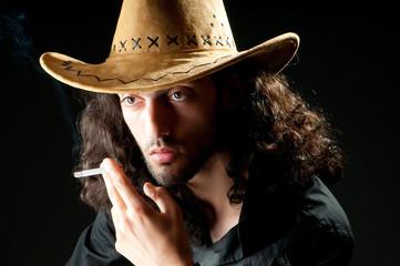Man in cowbow hat smoking