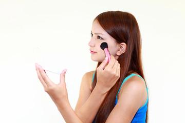 チークを塗る横顔の女性