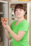 woman putting fresh eggs into fridge