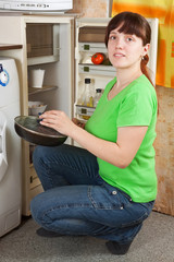 woman putting griddle into fridge