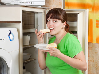 woman eating  pie from refrigerator