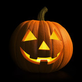 Halloween - carved pumpkin glowing in the dark