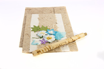 Artificial flower on mulberry card with bamboo pen on white back