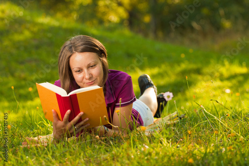 Beatiful woman with a book in the park