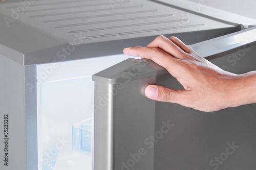 Leinwanddruck Bild hand opening refrigerator