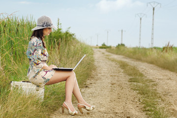 young lady with laptop spending time on a country road