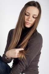 Ragazza bionda che guarda i suoi capelli su sfondo bianco