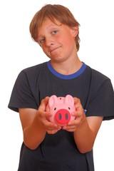 Skeptisch schauender Teenager mit Sparschwein