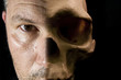 Scary Haalloween concept of half face half skull visible on dark