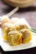 Dimsum on a white dish by a bamboo basket [chinese food]