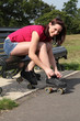 Beautiful girl ties roller skates on park bench