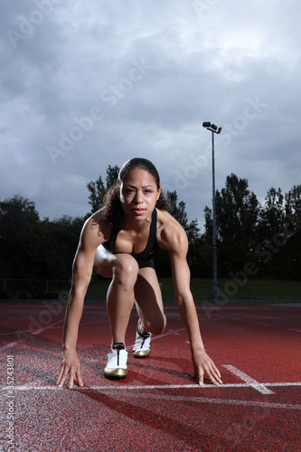Female athlete in starting position on track
