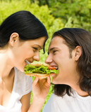 Young happy couple eating together outdoors