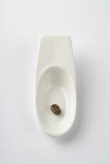 Vajilla, cuchara de cerámica con un grano de café
