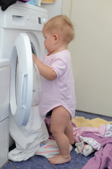 Little girl at the washing machine
