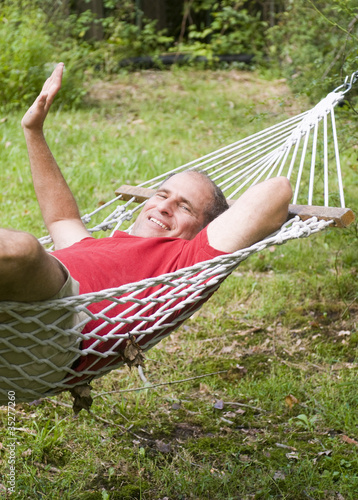smiling middle age man relaxing in hammock