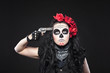 Serious woman in skull mask shot in head