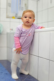 Toddler girl playing in a bathroom