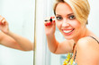 Smiling woman in bathroom applying mascara