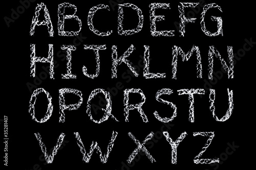 White chalk handwritten letters alphabet on blackboard