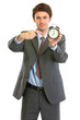 Modern businessman pointing on alarm clock