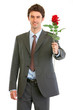 Smiling modern businessman with red rose in hand