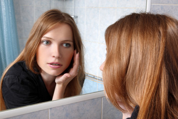 young woman in bath at front of a mirror inspected skin