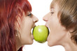 Close-up of happy couple biting a green apple from another sides